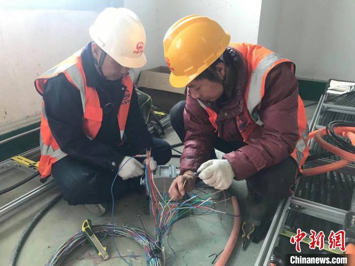 来自陕西宝鸡的马旭东(右一)与工友正在测试电缆线间绝缘。 刘鸿鹤 摄