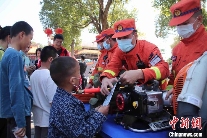 图为防火勤务中,谢海(右二)向小朋友认真讲解森林防火常识。福建省森林消防总队厦门驻防分队 供图